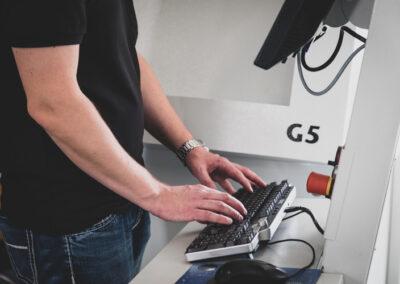 Mitarbeiter bedient die tastatur einer Lasergravurmaschine